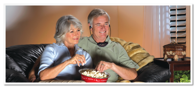 Man using TV Ears Headset while his wife watches TV comfortably.